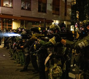 In this Friday, Sept. 18, 2020, file photo, Federal police try to take control of the streets during protests in Portland, Ore. (AP Photo/Paula Bronstein, File)