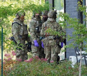 Royal Canadian Mounted Police officers prepare to enter an apartment complex in connection with the mailing of ricin to President Trump Monday, Sept. 21, 2020 in St. Hubert, Canada. (Ryan Remiorz/The Canadian Press via AP)