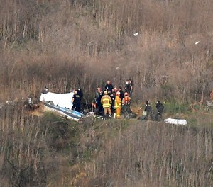 A body is covered, left, while another is seen at right at the scene of a helicopter crash that killed former NBA basketball player Kobe Bryant and eight others in Calabasas, Calif., Sunday, Jan. 26, 2020.