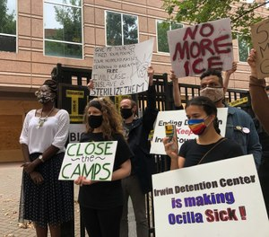 In this Tuesday, Sept. 15, 2020, file photo, Dawn Wooten, left, a nurse at Irwin County Detention Center in Ocilla, Georgia, speaks at a news conference in Atlanta protesting conditions at the immigration jail. (AP Photo/Jeff Amy, File)