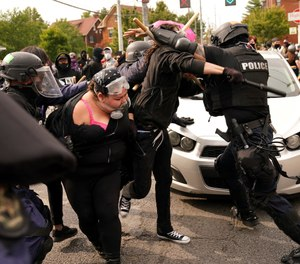 Police and protesters clash during a demonstration over a lack of charges against Louisville police in Breonna Taylor's death Wednesday, Sept. 23, 2020, in Louisville, Ky. (AP Photo/John Minchillo)