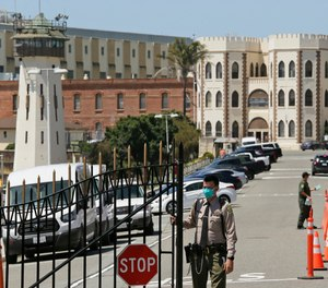 In this July 9, 2020 file photo, a correctional officer closes the main gate at San Quentin State Prison in San Quentin, Calif.