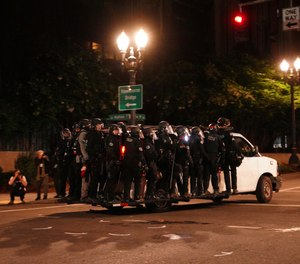 Portland Police line around a van and drive away from protesters rallying at the Mark O. Hatfield United States Courthouse on Saturday, Sept. 26, 2020, in Portland, Ore.