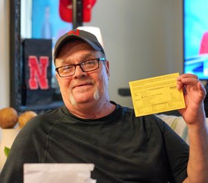 In this undated photo Wally Wolff holds up voter registration paperwork at his home in Omaha, Neb.