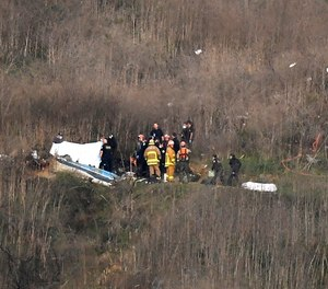 In this Jan. 26, 2020, file photo, a body is covered, left, while another is seen at right at the scene of a helicopter crash that killed former NBA basketball player Kobe Bryant and eight others in Calabasas, Calif.
