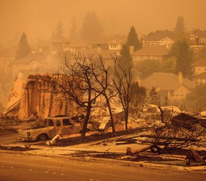 Homes leveled by the Glass Fire line a street in the Skyhawk neighborhood of Santa Rosa, Calif., on Monday, Sept. 28, 2020. Firefighter Grant Newnom defended his girlfriend's parents' Santa Rosa home from the blaze after finishing an extended 60-hour shift on Sunday. (AP Photo/Noah Berger)