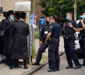 Members of the Orthodox Jewish community speak with NYPD officers, Wednesday, Oct. 7, 2020, in the Borough Park neighborhood of the Brooklyn borough of New York. (AP Photo/John Minchillo)