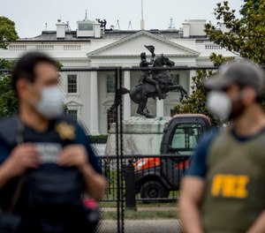 In this June 2, 2020, file photo the White House is visible behind a large security fence as uniformed Secret Service and FBI agents stand on the street in front of Lafayette Park in the morning hours in Washington. (AP Photo/Andrew Harnik, File)