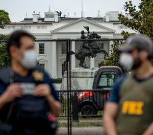 In this June 2, 2020, file photo the White House is visible behind a large security fence as uniformed Secret Service and FBI agents stand on the street in front of Lafayette Park in the morning hours in Washington.