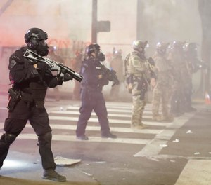 In this July 28, 2020, file photo, federal officers deploy tear gas and crowd control munitions at demonstrators during a Black Lives Matter protest at the Mark O. Hatfield United States Courthouse in Portland, Ore.