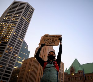 A protester holds a sign while listening to speakers outside Hennepin County Government Center in Minneapolis, Thursday, Oct. 8, 2020. (Aaron Lavinsky/Star Tribune via AP)