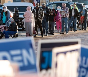 Voters line up outside the HUB to cast their ballots for early voting in the November presidential election Tuesday, Oct. 13, 2020, in downtown Tyler, Texas.