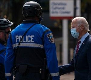 Former Vice President Joe Biden talks with Wilmington, Del., police officers as he departs The Queen theatre in Wilmington, Del., Monday, Oct. 19, 2020.