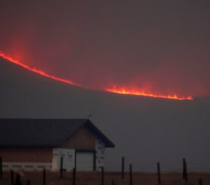 Flames rise from mountain ridges as a wildfire burns near Granby, Colorado, on Oct. 22, 2020.