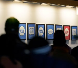 In this Oct. 23, 2020, file photo people lined up to vote or register to vote are shown next to signs in different languages at the King County election headquarters in Renton, Wash. Election officials are on high alert amid fears that U.S. polling stations could attract the same strain of partisan violence and civil unrest that erupted on American streets this year.