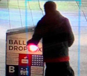 This surveillance image shows a man approaching a ballot drop box outside the Boston Public Library, early Sunday, Oct. 25, 2020, in downtown Boston.