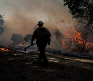 A firefighter prepares to put out hotspots while battling the Silverado Fire, Monday, Oct. 26, 2020, in Irvine, Calif. Orange County Fire Authority Chief Brian Fennessy said Tuesday that two firefighters who were critically injured in a burnover while battling the Silverado Fire are