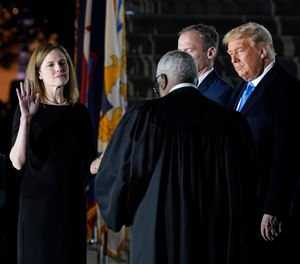 President Donald Trump watches as Supreme Court Justice Clarence Thomas administers the Constitutional Oath to Amy Coney Barrett on the South Lawn of the White House in Washington, Oct. 26, 2020.