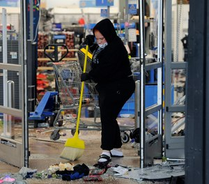 A woman cleans up debris at a Walmart, Wednesday, Oct. 28, 2020, that was damaged in protests in Philadelphia.