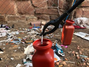 n this Aug. 9, 2019, file photo, a drug syringe found behind a vacant property in northeast Albuquerque, N.M., is placed into a container, as crews attempt to clear the lot of needles and other heroin paraphernalia.