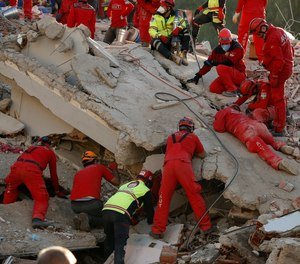 Members of rescue services search in the debris of a collapsed building for survivors in Izmir, Turkey, Sunday, Nov. 1, 2020. Rescue teams continue ploughing through concrete blocs and debris of collapsed buildings in Turkey's third largest city in search of survivors of a powerful earthquake that struck Turkey's Aegean coast and north of the Greek island of Samos, Friday Oct. 30, killing dozens and hundreds of others were injured.