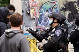 In this July 1, 2020 file photo, a police officer engages with a protester in Seattle, where streets had been blocked off in an area demonstrators had occupied for weeks.