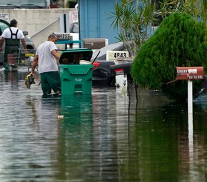 Residents clear debris from a flooded street in the aftermath of Tropical Storm Eta. A West Manatee Fire Rescue firefighter was shocked while responding to a fatal electrocution amidst flooding caused by the storm.