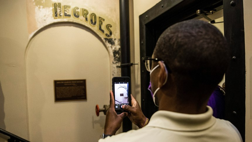 "Dannion McLendon takes a photo of the historical marker placed and sign that reads ""NEGROES"" at the Ellis County Courthouse in Waxahachie, Texas, on Monday, Nov. 17, 2020."