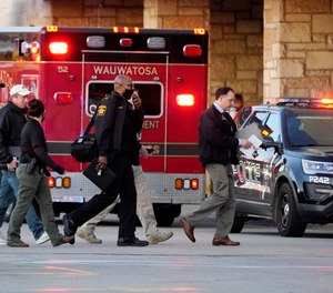 Police officials walk to the Mayfair Mall, Friday, Nov. 20, 2020, in Wauwatosa, Wis.