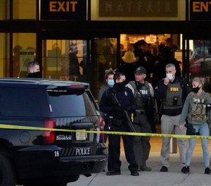 FBI officials and police stand outside the Mayfair Mall after a shooting, Friday, Nov. 20, 2020, in Wauwatosa, Wis.