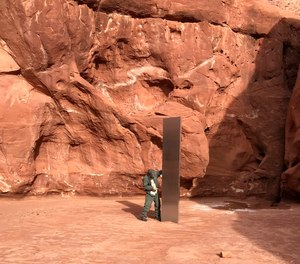 A Utah state worker inspects a metal monolith that was found installed in the ground in a remote area of red rock in Utah.