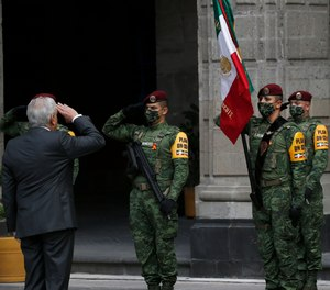Mexican President Andres Manuel Lopez Obrador salutes the flag during the commemoration of his second anniversary in office, at the National Palace in Mexico City, Tuesday, Dec. 1, 2020.