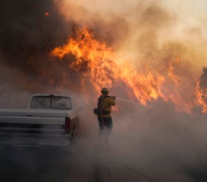 In this Oct. 26, 2020 file photo, a firefighter battles the Silverado Fire in Irvine, Calif. Two firefighters who were critically burned while battling the Silverado Fire were trying to set backfires amid extremely dangerous conditions, a new report from the Orange County Fire Authority states.