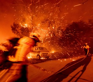 Firefighters battling the Bond Fire haul a hose while working to save a home in the Silverado community in Orange County, Calif., on Thursday, Dec. 3, 2020. Two fires have been injured battling the blaze, which has grown to 6,400 acres in less than two days.