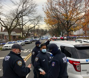 New York Police officers block off the street near the scene where a suspect was killed during a shootout with U.S. marshals in the Bronx that left two officers wounded, Friday, Dec. 4, 2020, in New York.