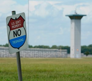 A no trespassing sign is displayed outside the federal prison complex in Terre Haute, Ind.