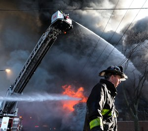 Firefighters work to extinguish a fire at a commercial building on Thursday, Dec. 10, 2020, in Chicago. Chicago Fire Department spokesman Larry Merritt says crews were called to flames shooting through the roof of Best Value Auto Body Supply Inc.