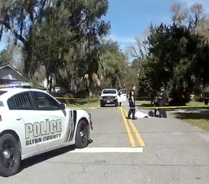 In this Feb. 23, 2020 image taken from body camera video, authorities stand over the covered body of Ahmaud Arbery, a 25-year-old Black man, who was shot and killed while while running in a neighborhood outside the port city of Brunswick, Ga.