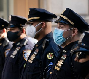 In this Oct. 5, 2020, file photo, NYPD officers stand during a service at St. Patrick's Cathedral in New York to honor colleagues who have died due to COVID-19 related illness.