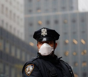 In this, May 1, 2020, file photo, a New York Police officer wears a mask to protect against coronavirus.