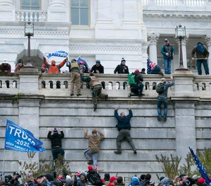 A group of demonstrators climb the west wall of the U.S. Capitol on Wednesday, Jan. 6, 2021. A Sanford firefighter is under investigation for allegedly participating in the mob that breached security and stormed the Capitol building.