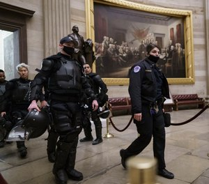 U.S. Capitol Police officers walk through the Rotunda as they and other federal police forces responded as violent protesters loyal to President Donald Trump stormed the U.S. Capitol in Washington, Wednesday, Jan. 6, 2021.