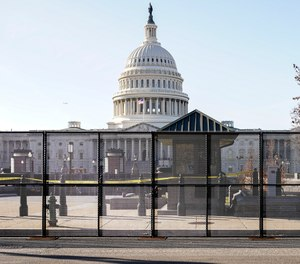 Capitol police officers stand outside of fencing that was installed around the exterior of the Capitol grounds, Thursday, Jan. 7, 2021 in Washington.