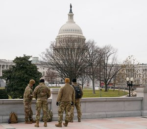 With the U.S. Capitol Building in view, members of the military stand in Washington, Friday, Jan. 8, 2021, in response to supporters of President Trump who stormed the Capitol.