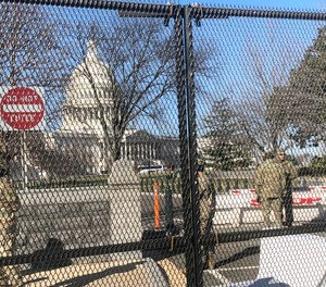 Members of the National Guard stand inside anti-scaling fencing that surrounds the Capitol, Sunday, Jan. 10, 2021, in Washington.