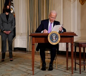 President Joe Biden signs executive orders in the State Dining Room of the White House, Tuesday, Jan. 26, 2021, in Washington. Vice President Kamala Harris listens at left.