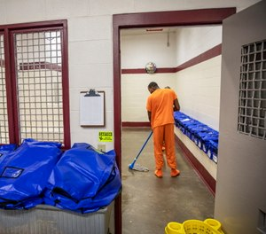 A detainee mops the floor at the intake station at the Stewart Detention Center in Lumpkin, Ga.