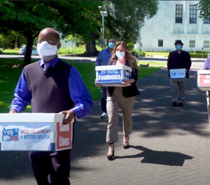 In this June 26, 2020, file photo taken from video, provided by the Yes on Measure 110 Campaign, volunteers deliver boxes containing signed petitions in favor of the measure to the Oregon Secretary of State's office in Salem, Ore.
