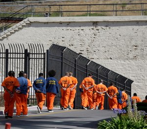 General population inmates walk in a line at San Quentin State Prison in San Quentin, Calif.