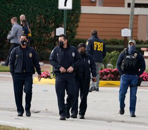 Law enforcement officers walk near the entrance to an apartment complex where a shooting wounded several FBI agents while serving an arrest warrant, Tuesday, Feb. 2, 2021, in Sunrise, Fla.